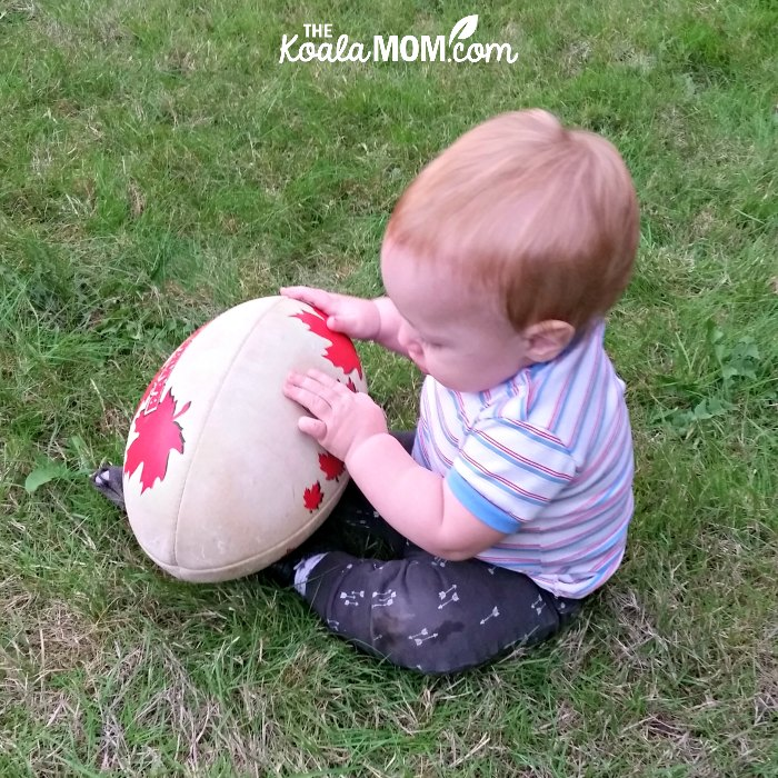 Baby boy holding a rugby ball (encourage your kids to play sports from a young age!)