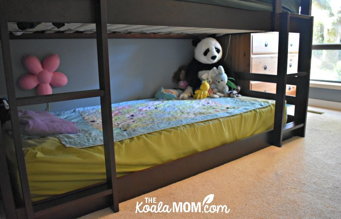 Stuffies and blanket on the mattress of the bottom bunk in a triple bunk bed.