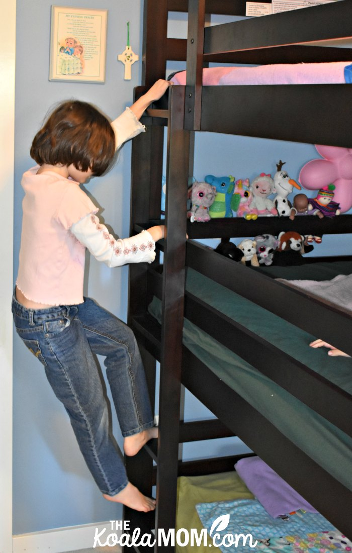 Girl climbing the ladder on her triple bunk bed.