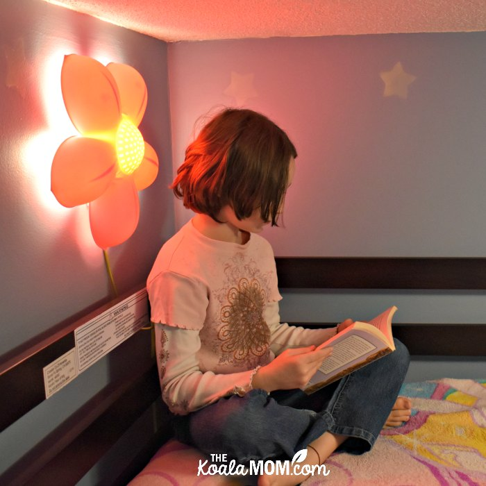 Gril reading by a flower light on the top bunk of a triple bunk bed.