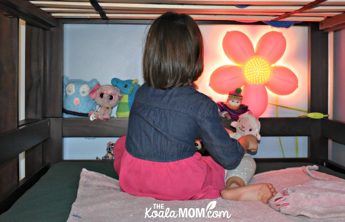 Girl playing with her stuffies in the middle bunk of a triple bunkbed.