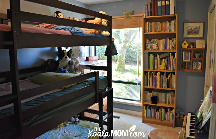 A girls blue bedroom with a triple bunk bed.
