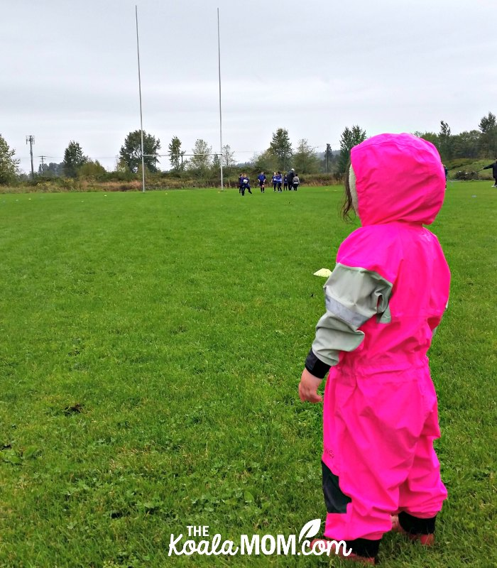 Toddler wearing her bright pink Oakiwear rain suit at her sisters' mini rugby game; the right gear can help encourage your kids to play sports.