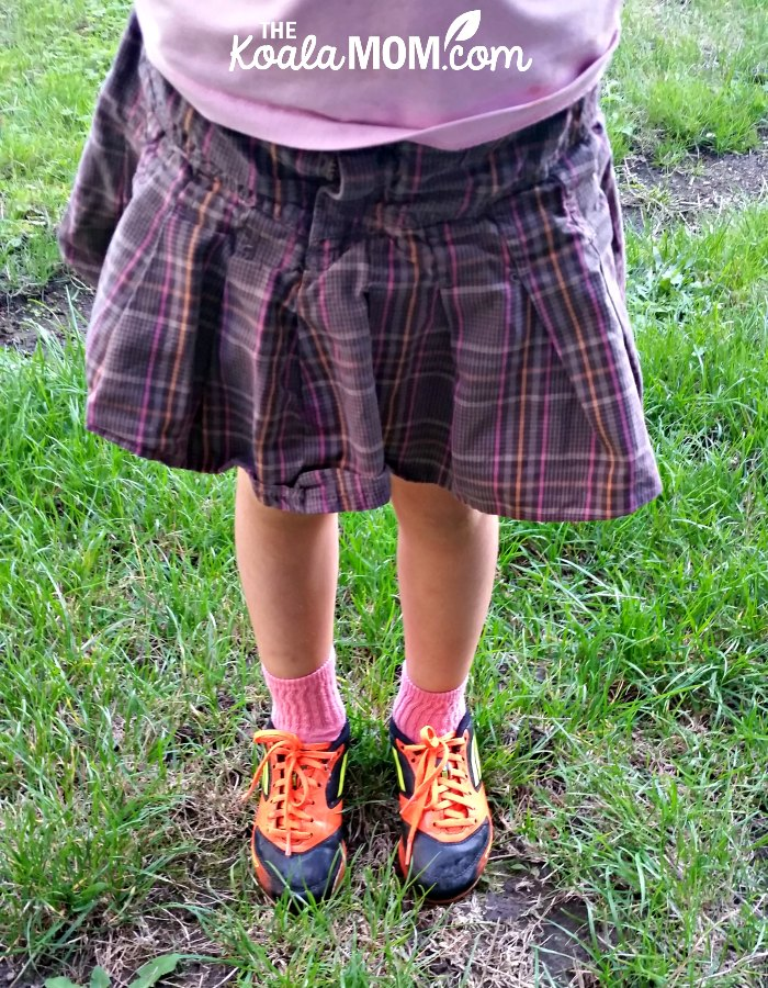 5-year-old wearing her orange rugby cleats and a plaid skirt - encourage your kids to play sports even if they give up easily!