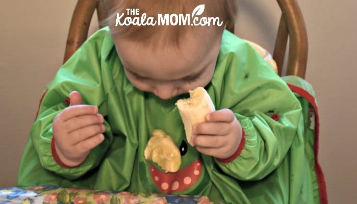 Baby feeding himself banana while wearing a Bibado bib.