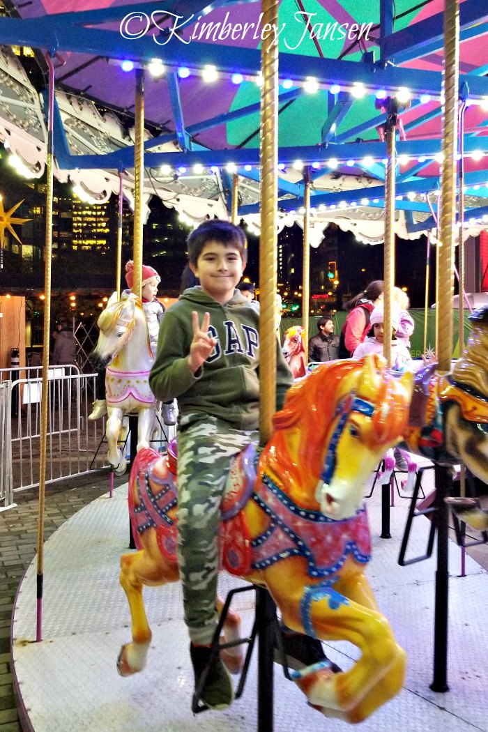 Boy riding the carousel at the Vancouver Christmas Market on a mother-son date night.