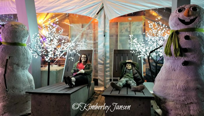 Mother and son relaxing on the giant loungers at the Vancouver Christmas Market during their mother-son date night.