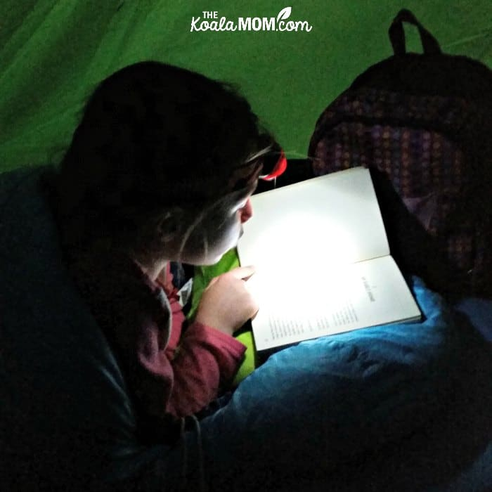 Girl reading a novel in the tent with a headlamp.