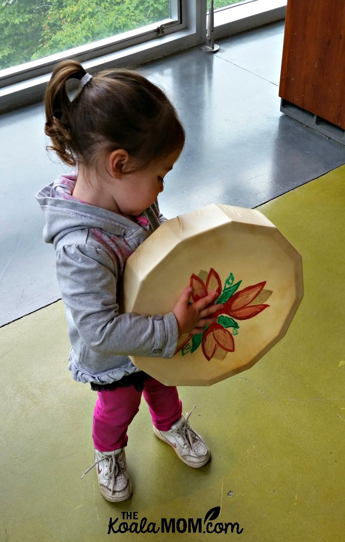 Toddler holding an aboriginal drum at the Squamish Lil'wat Cultural Centre in Whistler, BC.