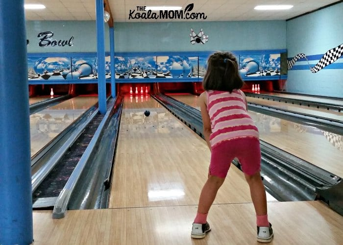 5-year-old watching her bowling ball roll down the lane.