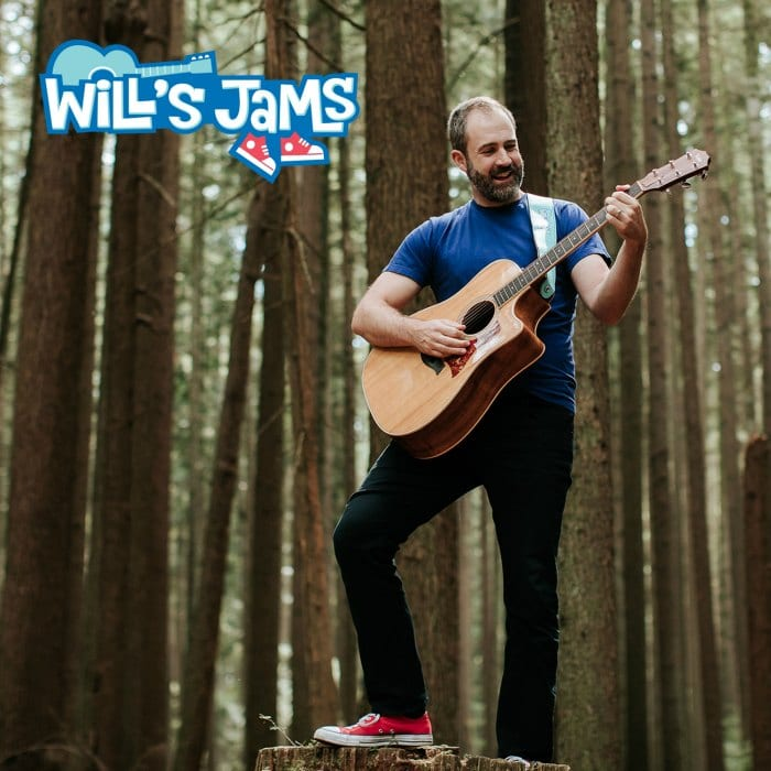 Will Stroet playing his guitar on a tree stump in the forest.