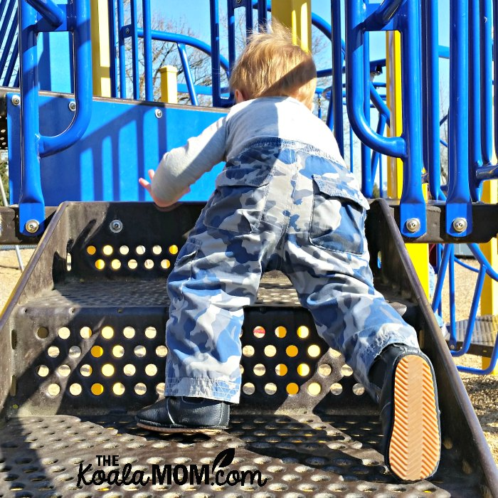 Baby climbing stairs on a playground.