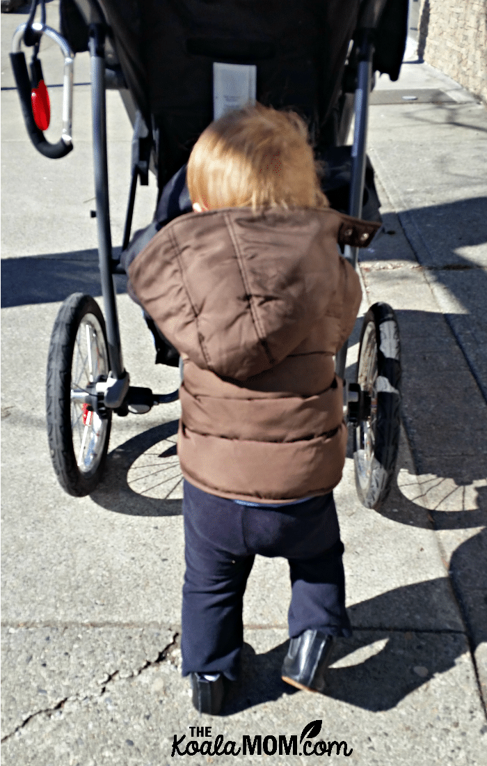Baby pushing his stroller while wearing a brown winter coat on a walk with Mommy.