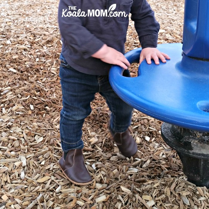 Baby standing beside spinning ride in his leather boot moccasins.