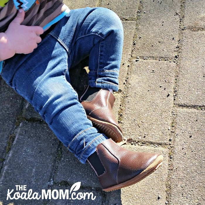 Baby wearing blue jeans and brown leather boots while sitting on cobblestones.