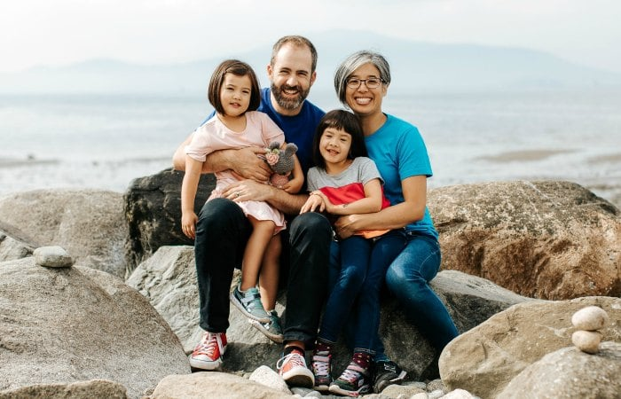 Kim The, Will Stroet, and their daughters posing on a beach.