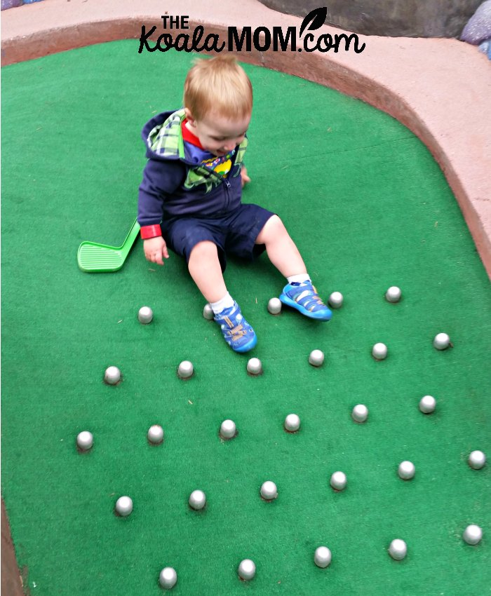 Toddler sliding down the mini golf course.