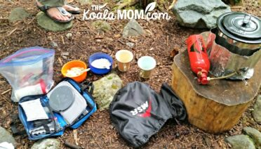 A backpacking kitchen: lightweight stove, fuel bottle, pot, utensils, and bowls with instant oatmeal and cups with instant coffee, waiting for water to boil.