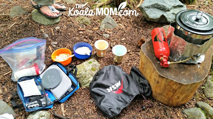 A backpacking kitchen on an overnight backpacking trip in BC: lightweight stove, fuel bottle, pot, utensils, and bowls with instant oatmeal and cups with instant coffee, waiting for water to boil.