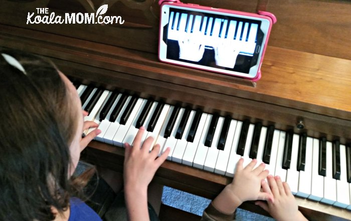 Girl learning piano online using a tablet.