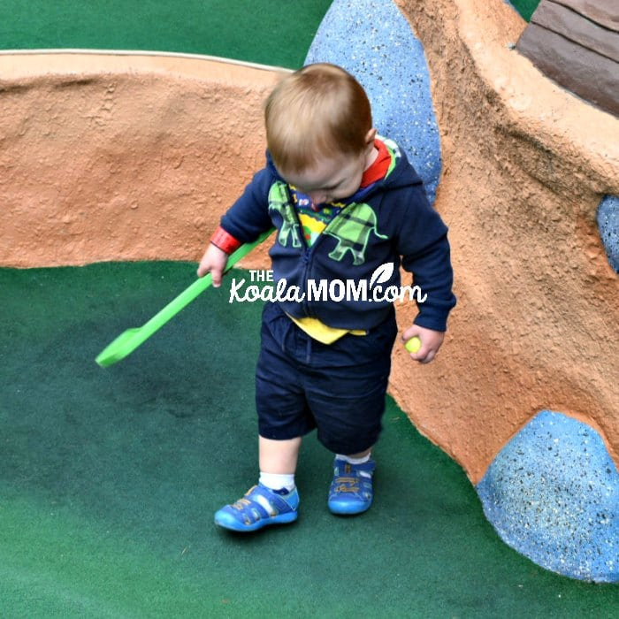 Toddler walking through mini golf course with a club and ball.