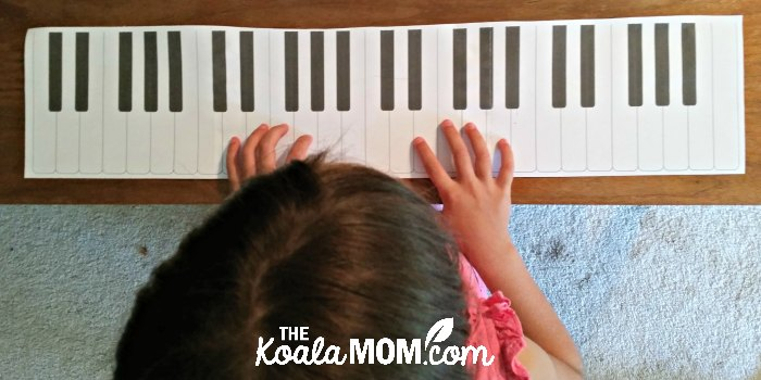6-year-old pretending to practice piano on her paper keyboard.
