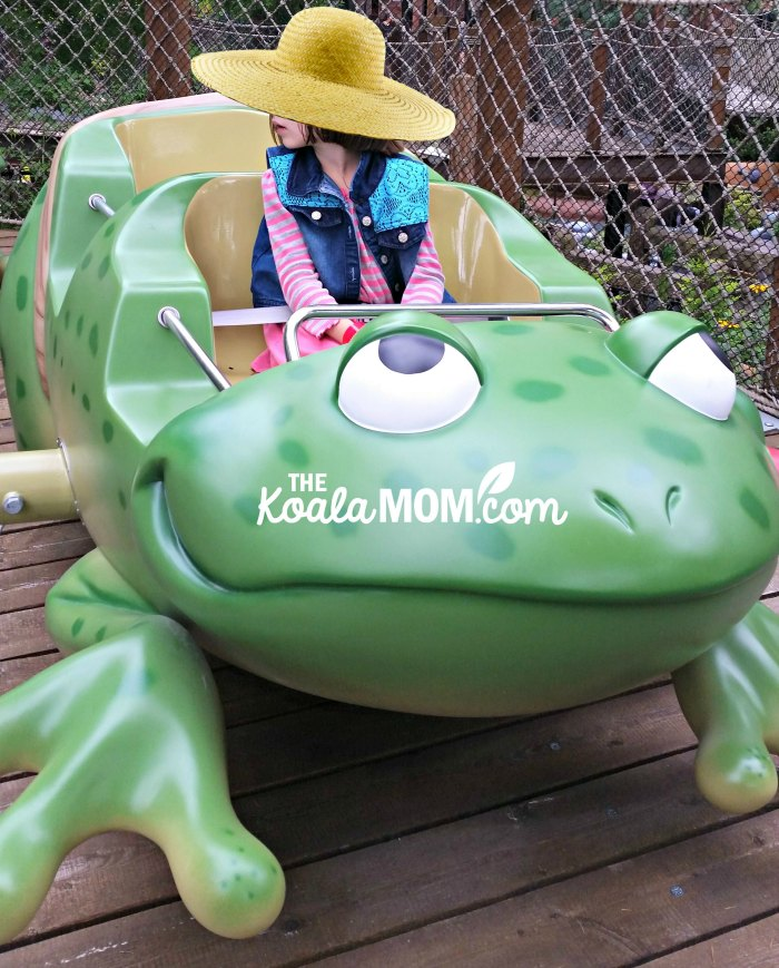 Girl riding on an amusement park frog.