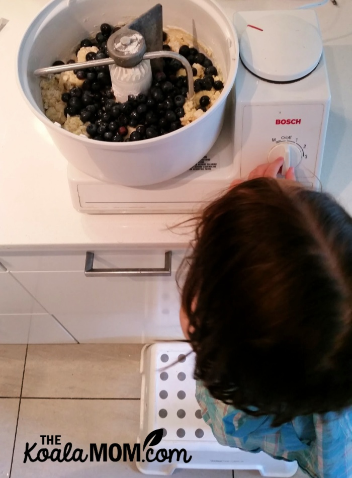 Toddler helping make muffins in a Bosch mixing machine.
