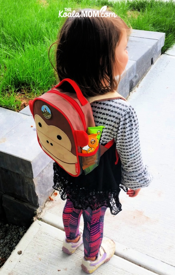 Toddler wearing a monkey backpack with FreeYumm snacks tucked in the pocket.