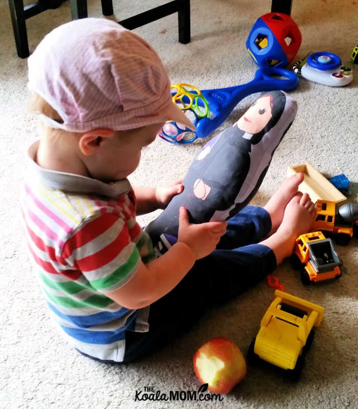 2-year-old boy holding a St. Elizabeth Ann Seton doll among his diggers and dumptrucks