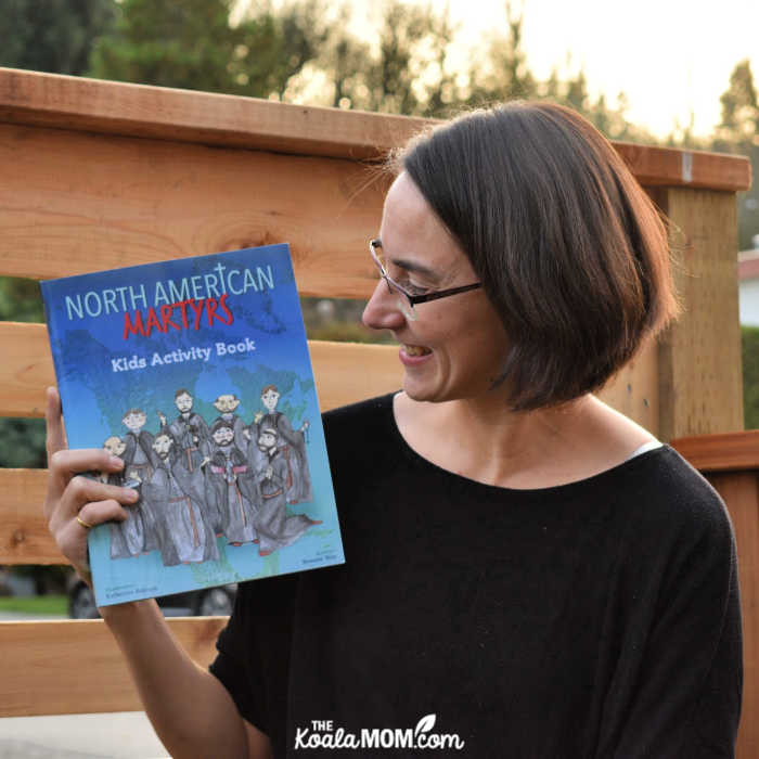 Bonnie Way holding her book, North American Martyrs Kids Activity Book