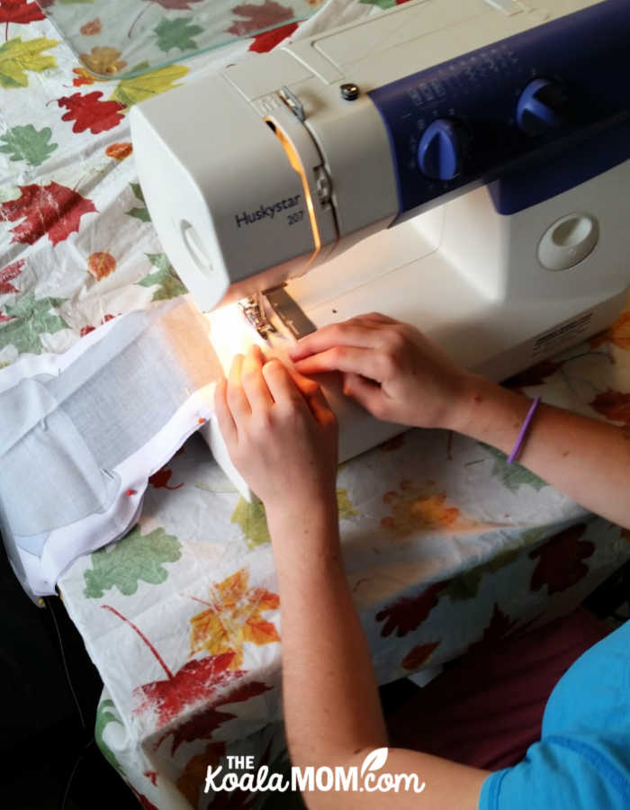 Sunshine sewing a doll for her siblings using a pattern from Faith and Fabric.