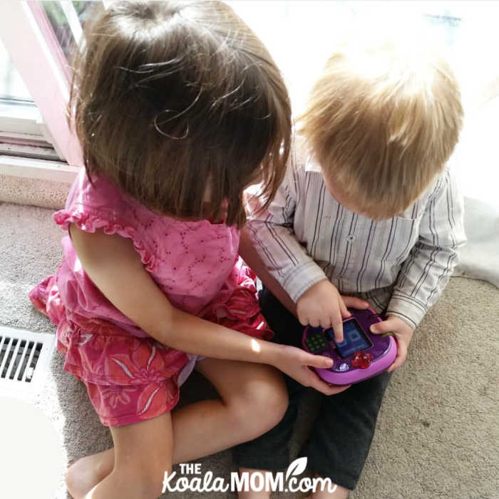 6-year-old and 2-year-old playing on an electronic learning system together.