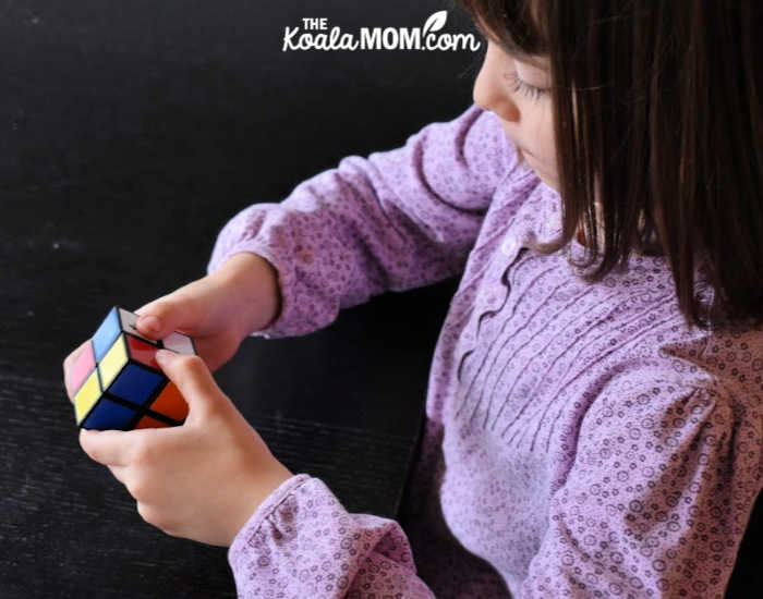 Six-year-old works on solving a cube puzzle.