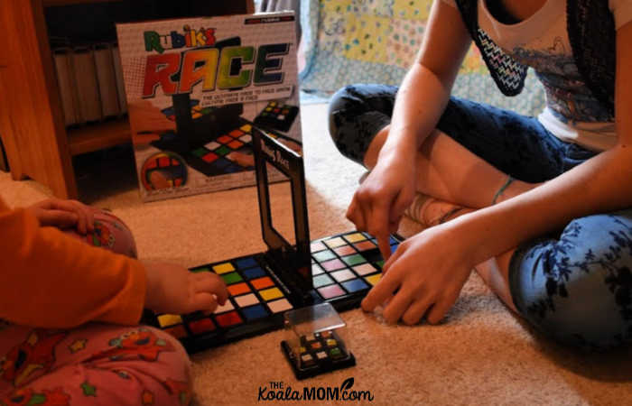 Two sisters have fun playing a board game together.