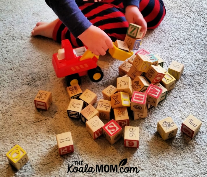 Toddler playing with his alphabet blocks.
