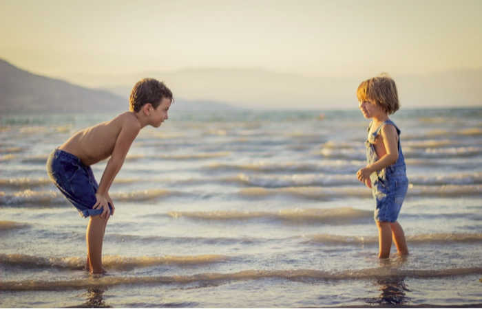 Two boys playing together at the beach. Photo by Limor Zellermayer on Unsplash