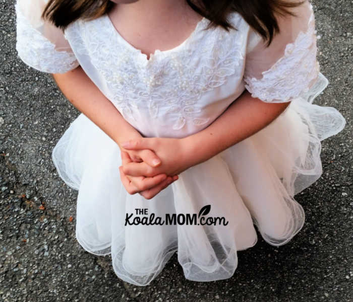 Girl wearing her First Communion dress with folded hands.