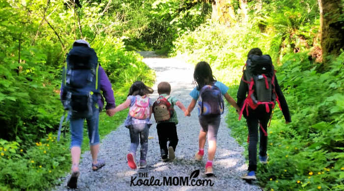 Five kids hiking together with their backpacks on.