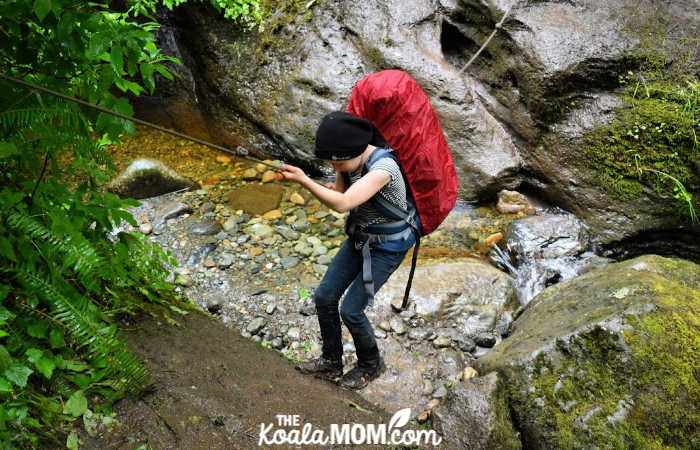 10-year-old Lily uses a rope to navigate a rocky ravine.