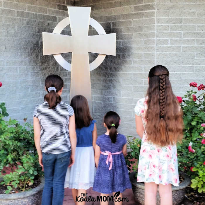 Girls looking at a cross in their Sunday best.