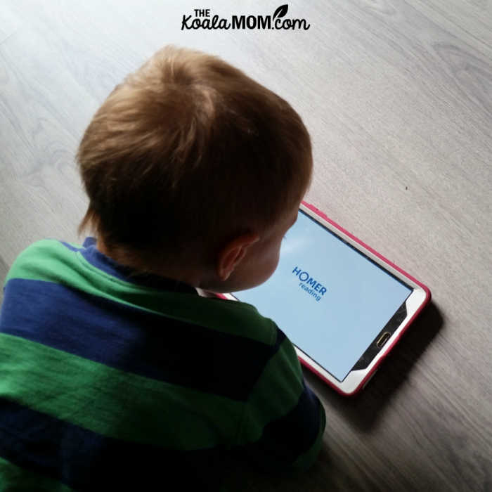 Toddler using HOMER Reading app on his tablet.