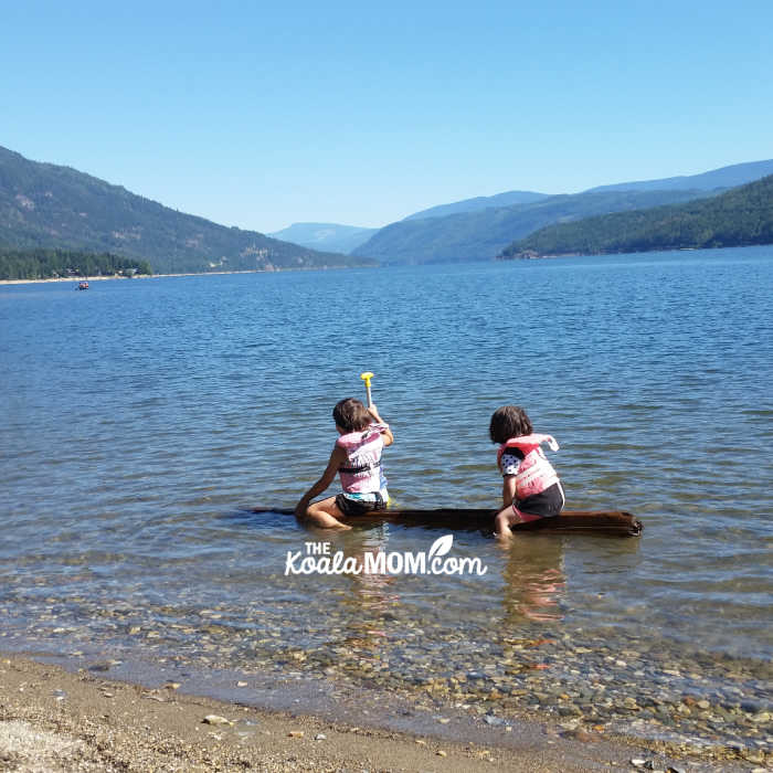 Two sisters in PFDs paddling a log on Shuswap Lake.