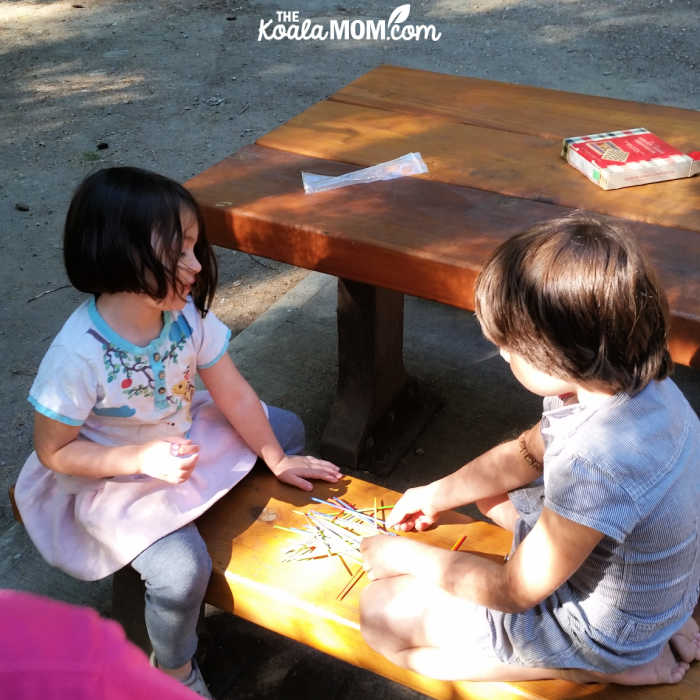 4-year-old and 7-year-old play pick-up-sticks at a picnic table.