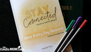 Stay Connected Journals for Catholic Women: Make Every Day Blessed - Living the Liturgical Year by Jennifer Frost with a Bible and three colourful pens.