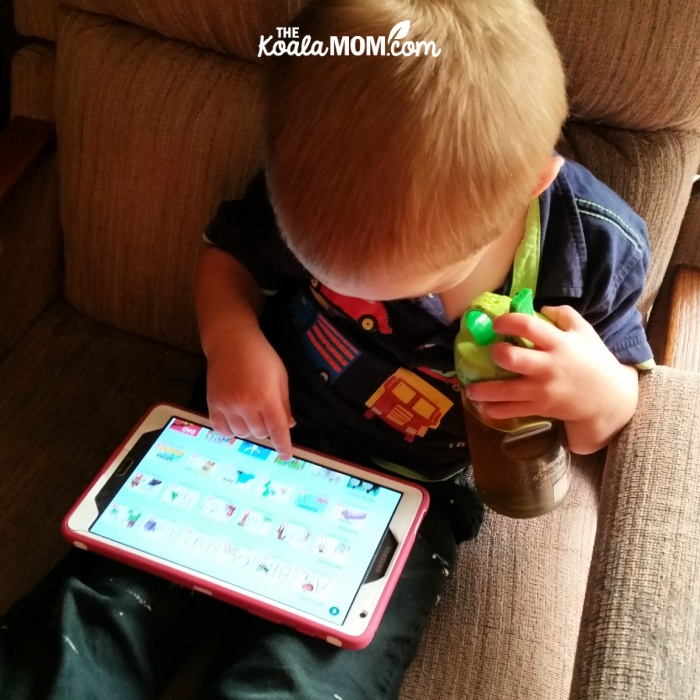 Toddler playing an educational phonics app on his tablet.