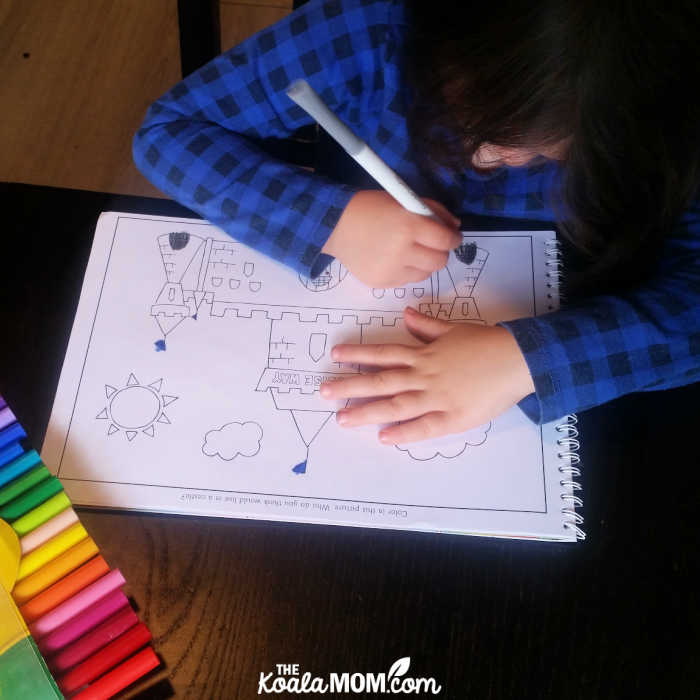 Kindergartener colours a castle in her personalized coloring book.