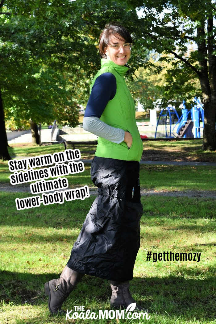 Stay warm on the sidelines with the ultimate lower body wrap! #getthemozy (Woman wears a green vest, boots, and a black Mozy - wearable blanket - wrapped around her waist.)