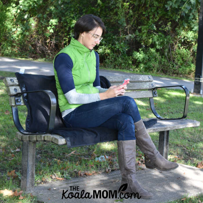 Woman sitting on the Mozy on a park bench while she reads a book on her phone.