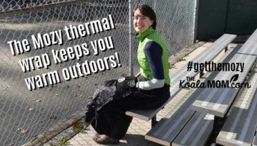 The Mozy thermal wrap keeps you warm outdoors, such as when you're at your child's sporting games like this mom sitting on stadium seating in her Mozy.